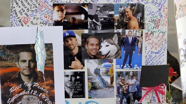 Photos and messages are seen at a roadside memorial at the site of the auto crash that took the life of actor Paul Walker.