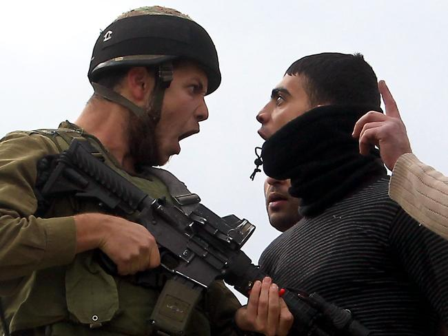 Across the great divide ... a Palestinian argues with an Israeli soldier after security forces intervened in clashes between Palestinian farmers and Israeli settlers.