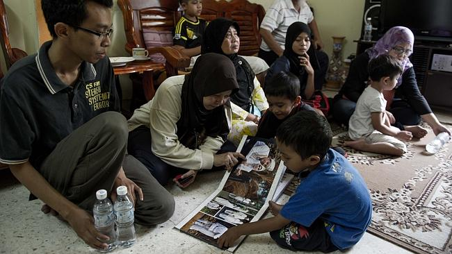 Family members of 34-year-old Norliakmar Hamid, a passenger on a missing Malaysia Airlines Boeing 777-200 plane, gather at their home and look through a wedding album in Kuala Lumpur.