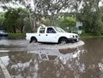 A motorist drives through floodwaters on Paringa Parade, Old Noarlunga at 8am on Thursday. Picture: Stephen Laffer