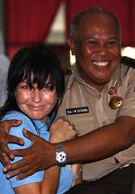 Convicted Australian drug smuggler Schapelle Corby gets a hug from senior prison warder as they watch Olympic Games competition during a pre-Independence Day fun and games event at Kerobokan Jail in Denpasar on Indonesian island of Bali.