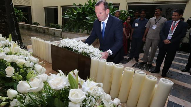 Prime Minister Tony Abbott lays a wreath at a memorial to those killed during a 2008 terrorist attack on the Taj Mahal Palace Hotel in Mumbai, India.