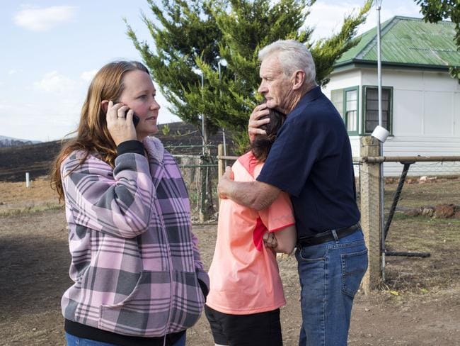 Samantha Truesdale talks to a neighbour on the phone while her daughter Abby is consoled by her grandfather. Picture: Sean Davey.