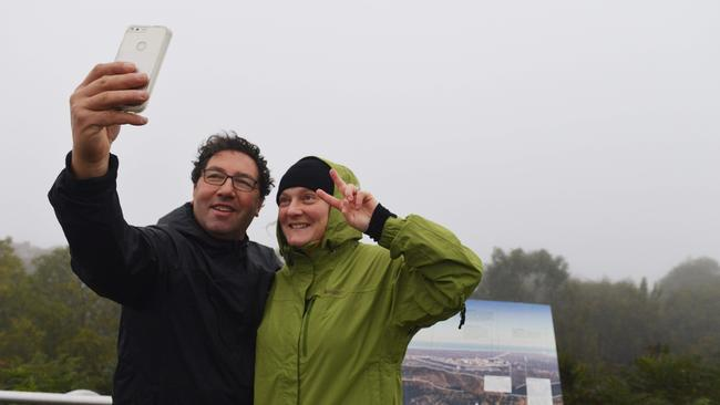 Regular Mt Lofty walkers George and Esme Savva of Aldgate stop for a panoramic selfie at the summit near Toowoomba despite the fog, on Monday. Picture: AAP Image/Brenton Edwards.