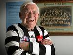 Collingwood legend Lou Richards beside a framed photo of the Magpies' 1896 premiership team. Picture: David Caird