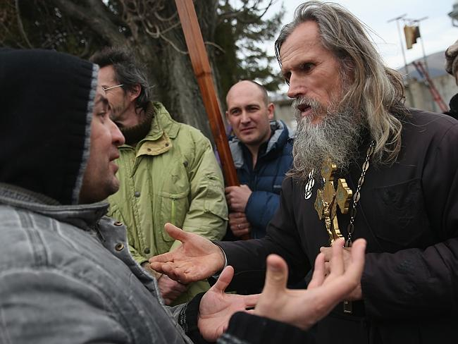Culture clash ... a pro-Russian man argues with an Orthodox priest outside a Ukrainian military base that has been surrounded by several hundred soldiers in Crimea. Picture: Sean Gallup