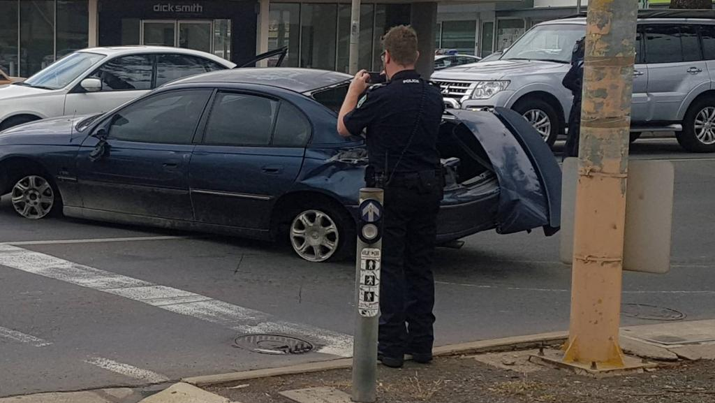 A police officer photographs the stolen car after it crashed at Glenelg East, on the corner of Brighton Rd and Anzac Highway. Pic: Damian Reed