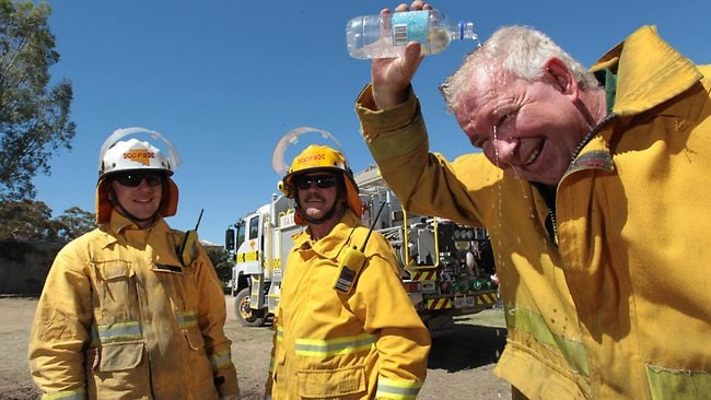 James Mackay of Stansbury, right, does his best to keep cool near a fire site in the Clare Valley as Lachlan Hennekan and Peter Bywaters look on. Picture: DEAN MARTIN