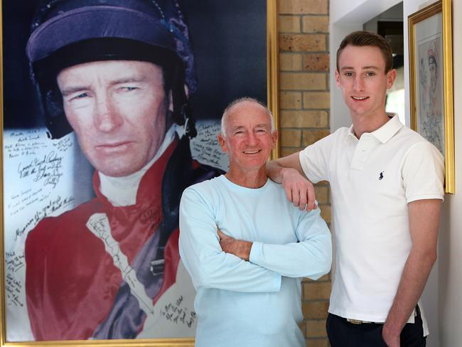 Mick Dittman and son Luke stand in front of a huge portrait of the champion jockey. Picture: Jono Searle