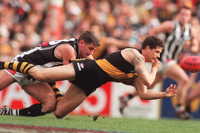 Richmond's Clay Sampson handballs clear of Collingwood's Gavin Crosisca. Picture: Karen Dodd