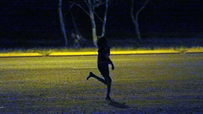 A young girl runs past a petrol station in Tennant Creek after dark. Children as young as seven roam the streets in Tennant Creek.