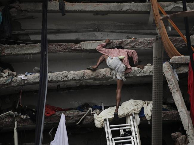 A Bangladeshi rescue volunteer climbs a section of the collapsed garment factory in April 2013.