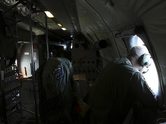 An observer looks out a window onboard a RNZAF P3 Orion during the search operations for missing Malaysia Airlines Flight MH370 in Southern Indian Ocean on April0 4, 2014.