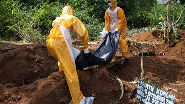 A team of funeral agents specialised in the burial of victims of the Ebola virus put another body in a grave. (AFP PHOTO FLORIAN PLAUCHEUR) Source: AFP