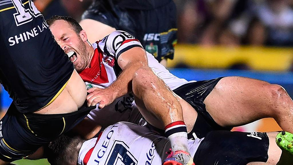 Ian Henderson of the Roosters has his lower leg broken while trying to tackle Ethan Lowe.