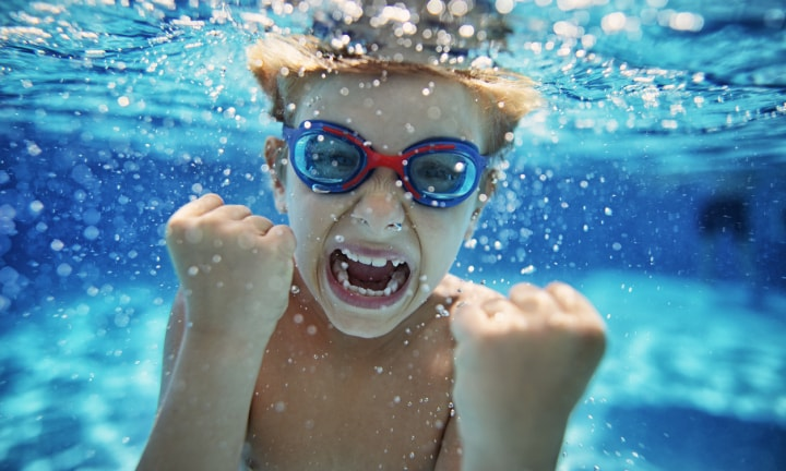 Little boy aged 6 swimming underwater. The boy is screaming at the camera with strong emotion.