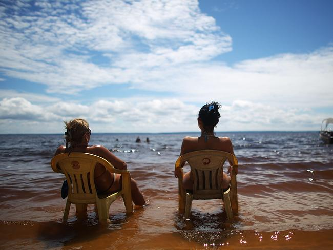 Two women sunbathe on the Praia da Lua beach in Manaus.