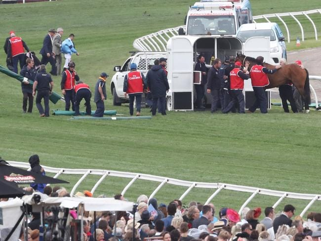 Jockey Joao Moriera is taken from the track after he fell on racehorse Regal Monarch in race 4.
