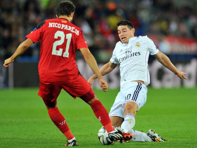 Real Madrid's Colombian forward James Rodriguez vies with Sevilla's Argentinian defender Nicolas Pareja (L) during the UEFA Super Cup.