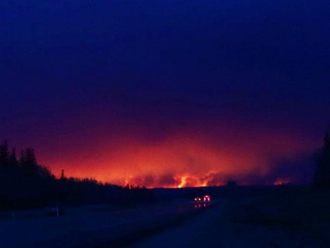 A plume of smoke hangs in the air as forest fires rage on in the distance in Fort McMurray, Alberta. Picture: AFP