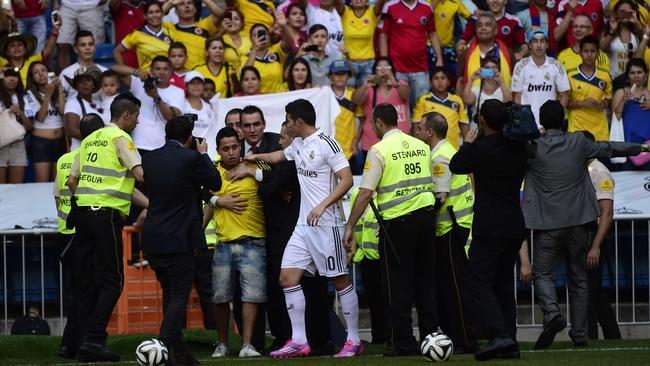 Colombian striker James Rodriguez prevents security from taking away an over-zealous fan