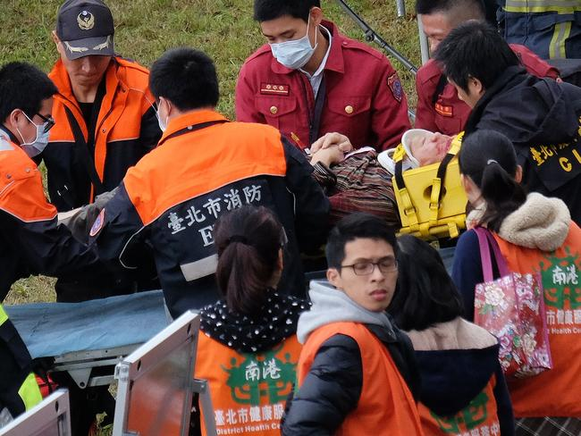 An injured passenger ... stretchered by emergency personnel along the river bank. Picture: AFP