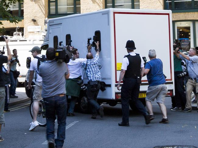 On his way to jail ... photographers chase the van taking Rolf Harris from court to prison.