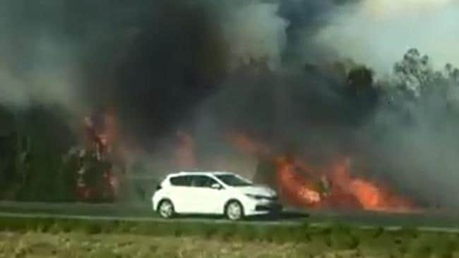 A car drives past the bushfire raging at Caloundra. Picture: Sunshine Coast Daily