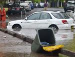 A worker (L) looks on past inundated cars on a flooded street after a storm in the eastern suburbs of Sydney on December 16, 2015. Sydney was smashed by a tornado-like storm with hail as big as golf balls and winds gusting at 200 kilometres (124 miles) an hour causing havoc with two people requiring treatment -- one for shock and one for a head wound -- in the hardest-hit suburb of Kurnell, an ambulance official said. AFP PHOTO / Peter PARKS