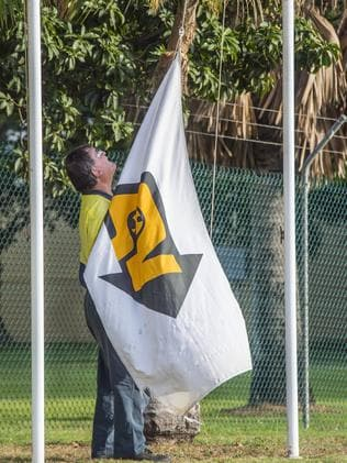 A worker hoists the flag at Queensland Nickel's plant north of Townsville. Picture: Brian Cassey