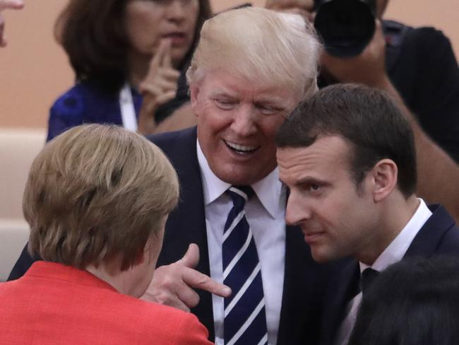 Donald Trump chats amiably with the German and French leaders backstage. Picture: Photo/Markus Schreiber