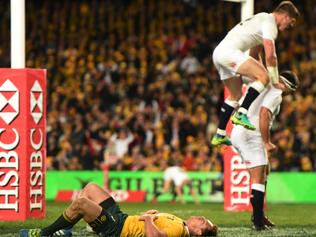Owen Farrell of England celebrates the try of Jamie George by leaping on him as Australia's Dane Haylett-Petty lays on the ground during the 3rd test between Australia and England at the Sydney Football Stadium in Sydney, Saturday, June 25, 2016. (AAP Image/Dean Lewins) NO ARCHIVING
