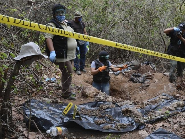 Forensic workers pauses dig up bodies at a site where a mass grave was found in the Pacific resort city of Acapulco, Mexico, Thursday June 9, 2011.