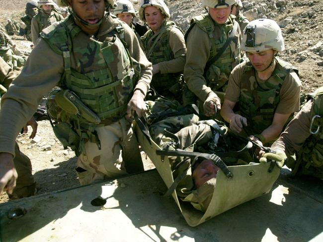 Casualty of war ... US soldiers carry a comrade wounded in a Taliban ambush.