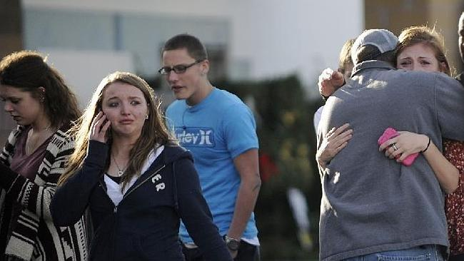 Chris Foster, right, hugs his daughter Devan, a senior, after they reunited at the Kings Sooper parking lot of Arapahoe High School. Picture: AP/The Denver Post, Cyrus McCrimmon