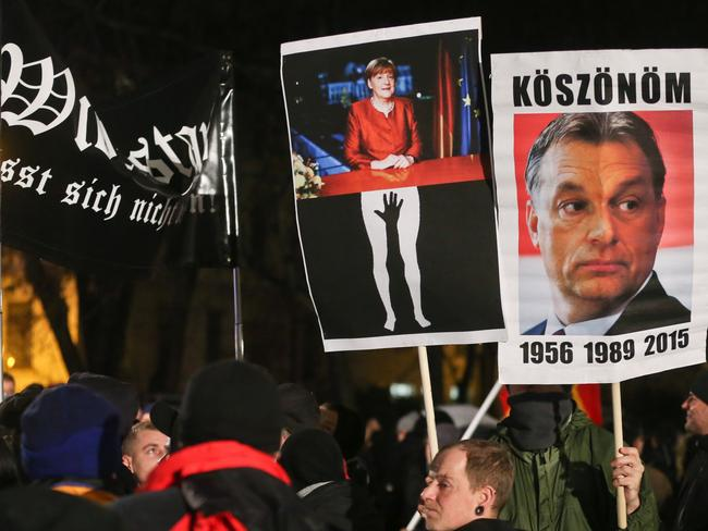 """Backlash ... A poster of German Chancellor Angela Merkel, centre, is seen next to a poster of the Hungarian Prime Minister Viktor Orban, right, saying """"Thank you"""" in Hungarian at a rally of the Patriotic Europeans Against the Islamisation of the Occident."""