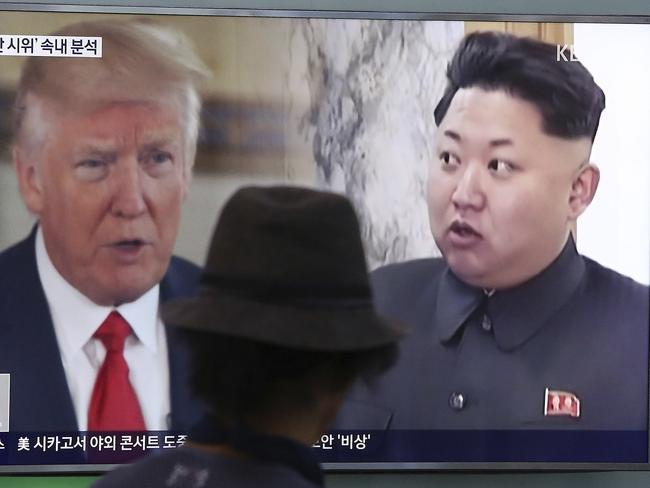 A man watches a television screen showing US President Donald Trump, left, and North Korean leader Kim Jong-un. Picture: AP