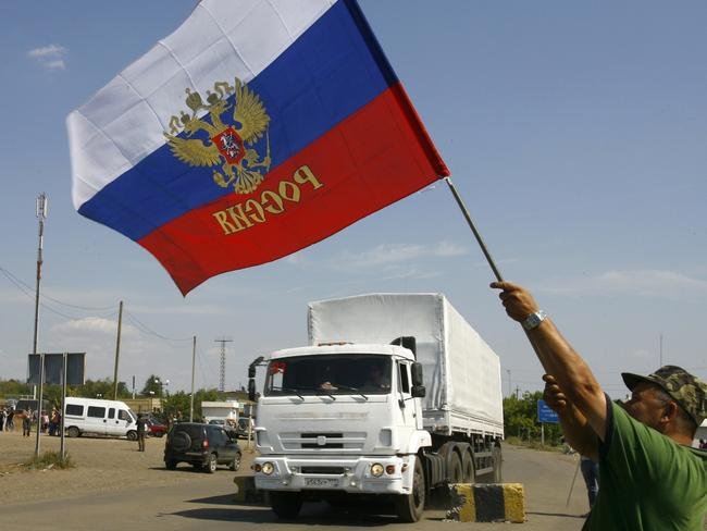 A local resident holds a Russian national flag as lorries, part of a Russian humanitarian convoy cross the Ukrainian border at the Izvarino custom control checkpoint on Friday. AFP PHOTO / SERGEY VENYAVSKY