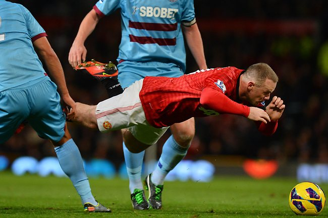 Manchester United's Wayne Rooney (R) falls as he vies with West Ham United's Winston Reid at Old Trafford. Picture: Ben Stansall