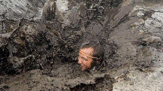 Competitors up to their neck in muck on the The Mud Mile. Picture: Brad Cooper