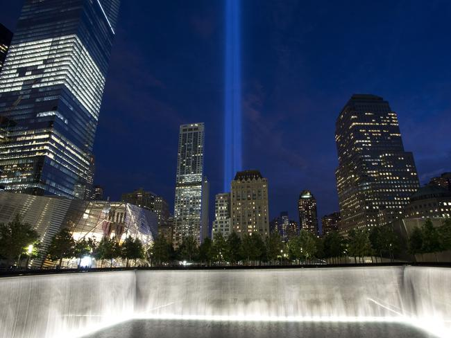 The Tribute in Light rises behind buildings adjacent to the 1 World Trade Center and a reflecting pool at the National September 11 Memorial. The tribute, an art installation of 88 searchlights aiming skyward in two columns, is a remembrance of the Sept. 11, 2001, attacks. (AP Photo/Mark Lennihan)