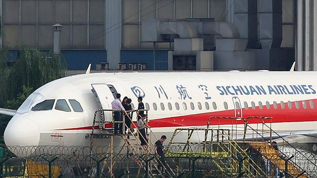 Employees check the Sichuan Airlines Airbus A319 after an emergency landing, after a co-pilot was sucked halfway out of the aircraft. Picture: AFP