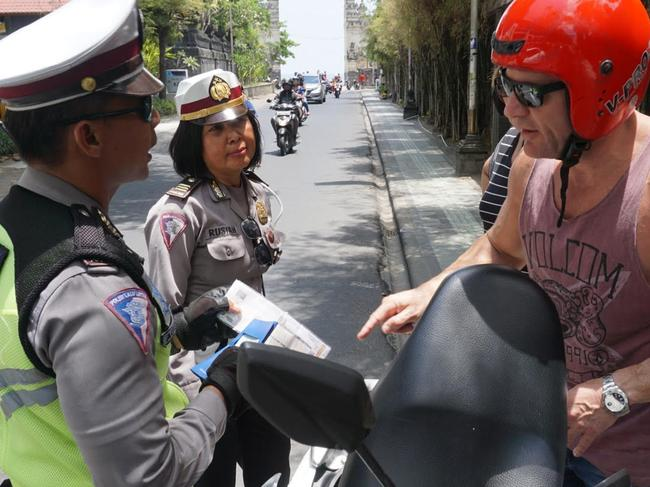 Traffic police stopping aussies in Bali today who are riding motorbikes. This is Matt Beckwith and Allison Beckwith. Will also send some video. He has a motorbike licence from Australia and rides a motorbike in Australia. And both were wearing helmets. The only question was that he had only a copy, not the original of the motorbike registration papers, given to him by the rental company. They told him to go back and get the original of the registration papers and carry them with him. Picture: Komang Erviani