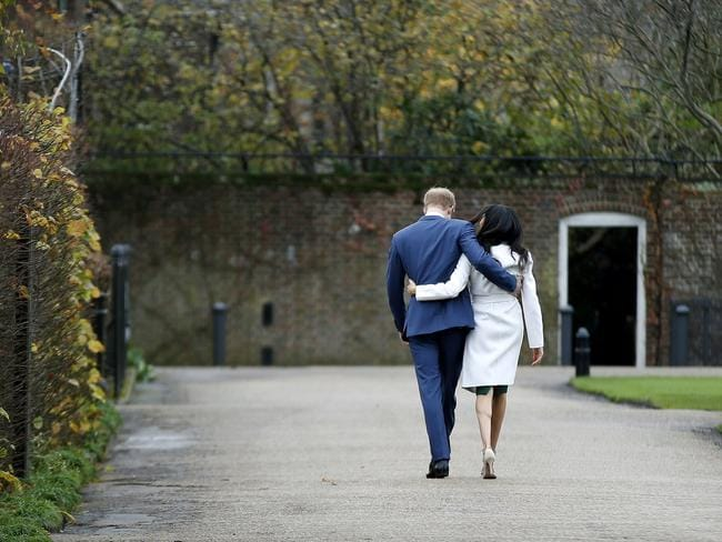 Prince Harry and Meghan Markle walk back into Kensington Palace after posing for the cameras. Picture: AP/Alastair Grant