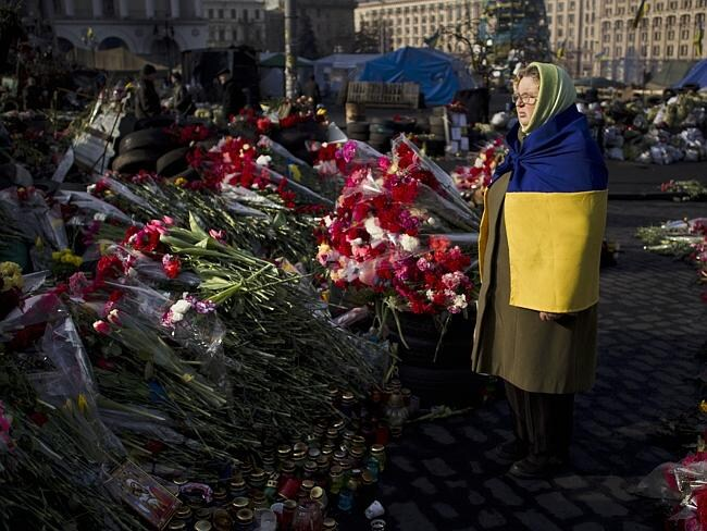 Lives lost...A woman draped with a Ukrainian national flag looks at flowers and messages left to those killed in recent clashes in Kiev's Independence Square. Picture: AP