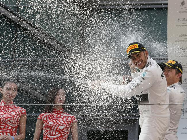 Mercedes driver Lewis Hamilton and teammate Nico Rosberg spray each other.