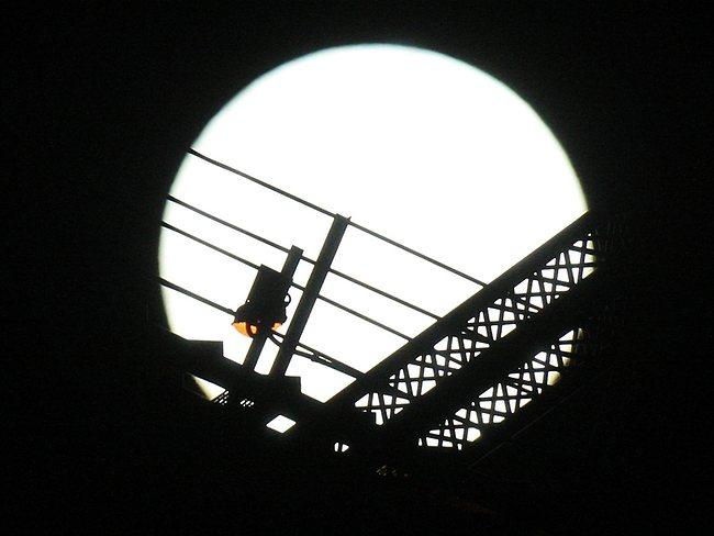 Moon shining through Story Bridge. Picture: Adam Smith
