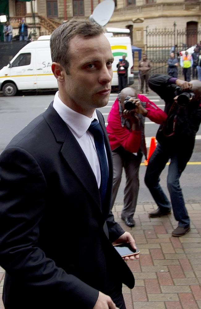 Arriving to court ... Oscar Pistorius flanked by media outside the Pretoria high court.