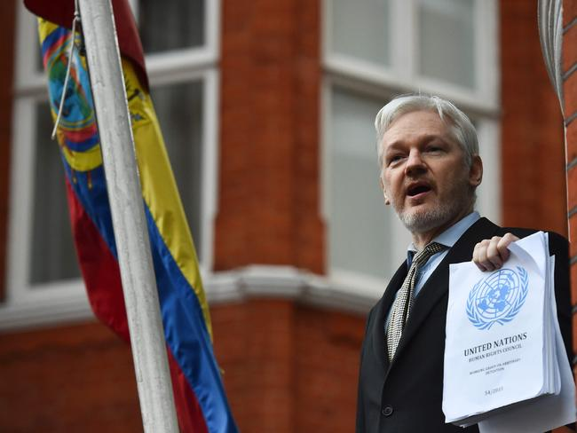 WikiLeaks founder Julian Assange addresses the media holding a printed report of the judgment of the UN's Working Group on Arbitrary Detention on his case from the balcony of the Ecuadorean embassy in central London. Picture: AFP