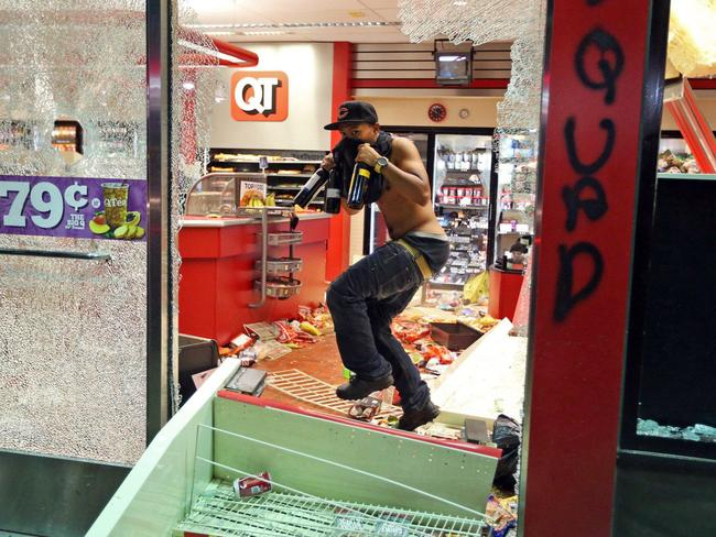 A man leaves a store that has been looted after the vigil for 18-year-old Michael Brown. Picture: AP